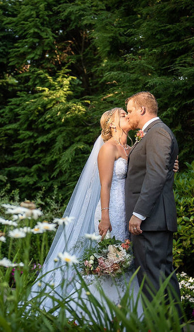 bride and groom kissing by a water fountain