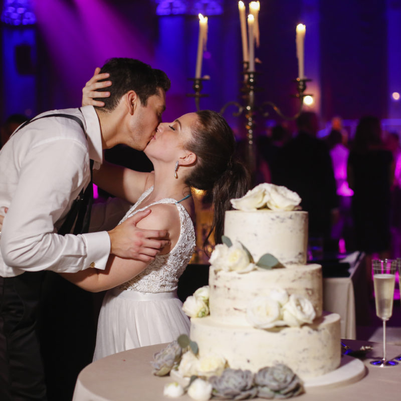 bride and groom embracing in front of wedding cake