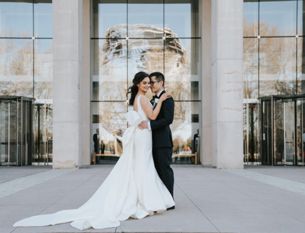 bride and groom embracing outside of the queens museum entrance