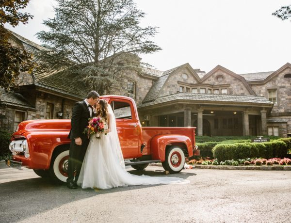 bride and groom embracing in front of antique car