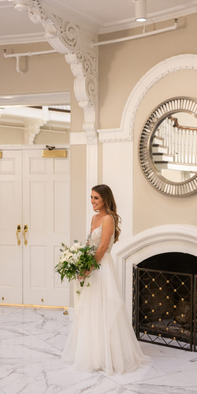 bride holding bouqet in front of a fireplace