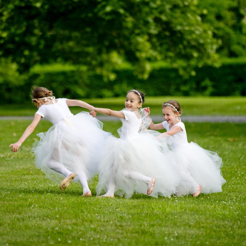 young girls wearing dresses running in the grass and smiling