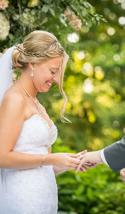 bride putting a ring on a grooms hand
