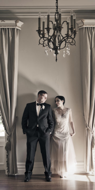 bride and groom standing against a wall staring at each other