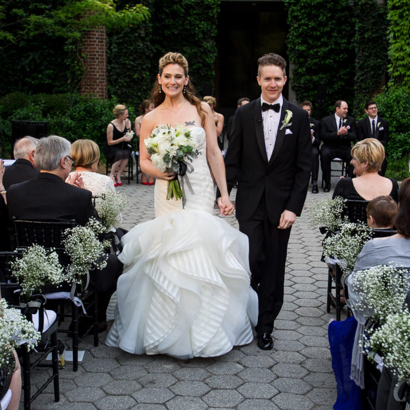 brid and groom walking down the aisle holding hands and smiling