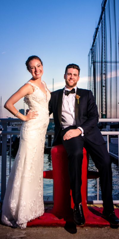 bride and groom smiling standing outside on a pier